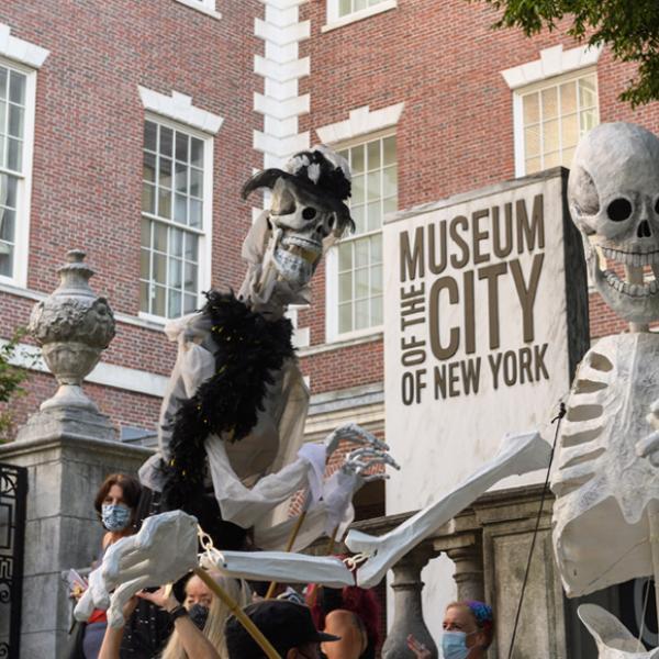 """Deux grandes marionnettes squelettes se font face. Il y a un panneau avec les mots """"Musée de la ville de New York"""" derrière eux."""