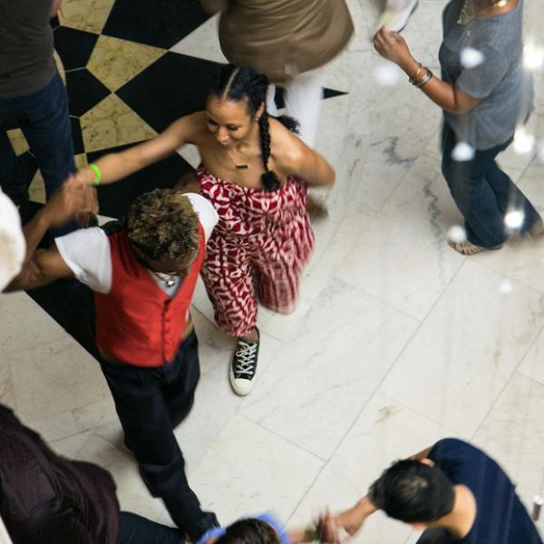 젊은 여자와 춤을 추는 젊은 남자의 오버 헤드 사진. 그들은 손을 잡고 있습니다.