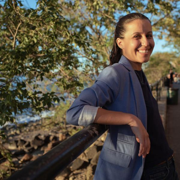 Tiffany Cabán is smiling and leaning in front of a park bridge. She is wearing a bluish gray blazer and a black blouse. Her hair is tied back in a ponytail.