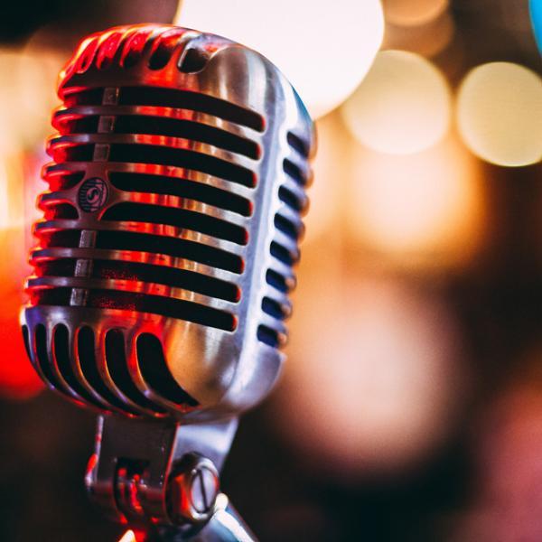 Un microphone d'argent mis au point sur un arrière-plan flou. Il y a des lumières jaunes, rouges et bleues floues dans des formes indiscernables en arrière-plan.