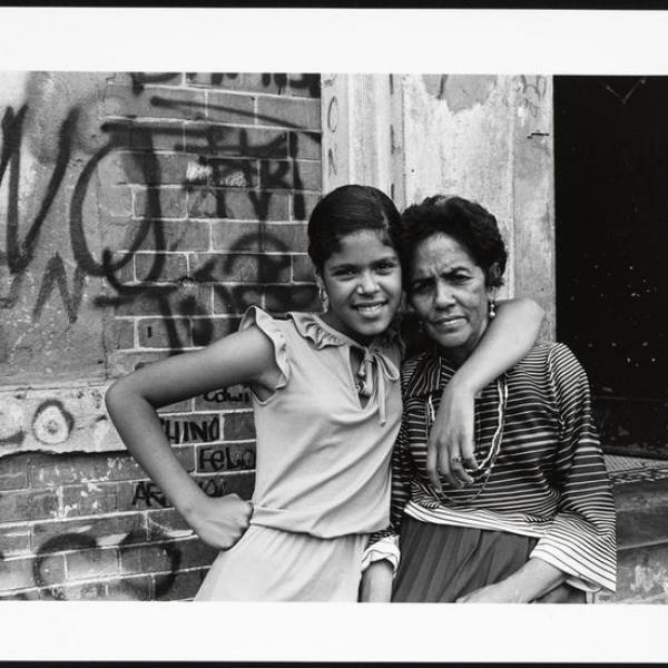 Two women pose in front of a graffitied building in the South Bronx of New York City