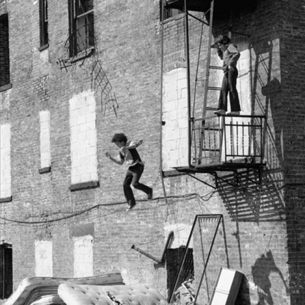 A street play photograph by Martha Cooper of a boy jumping from fire escape at the Lower East Side.