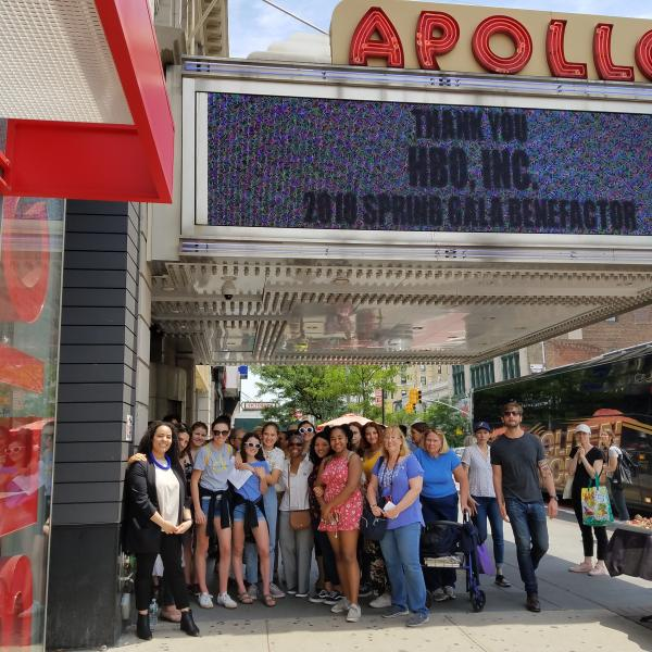 A tour group standing under the marquee of the Apollo Theater