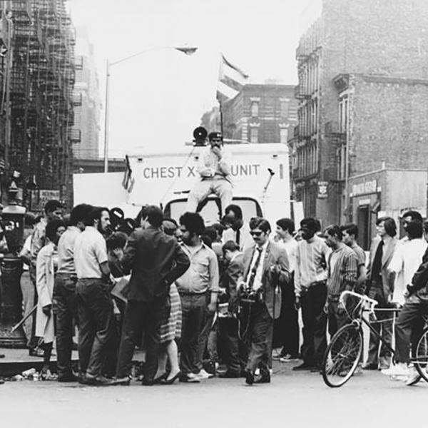 A group of young activists and journalists stand in front of a mobile x-ray truck, which is flying a Puerto Rican flag.