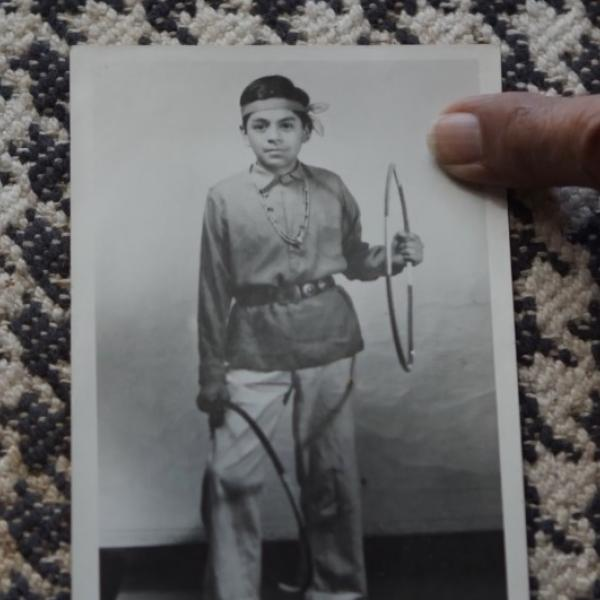black and white photograph of a young Native boy holding a hoop in his left hand, and another hoop around his right leg. A finger is pointing at the photograph.