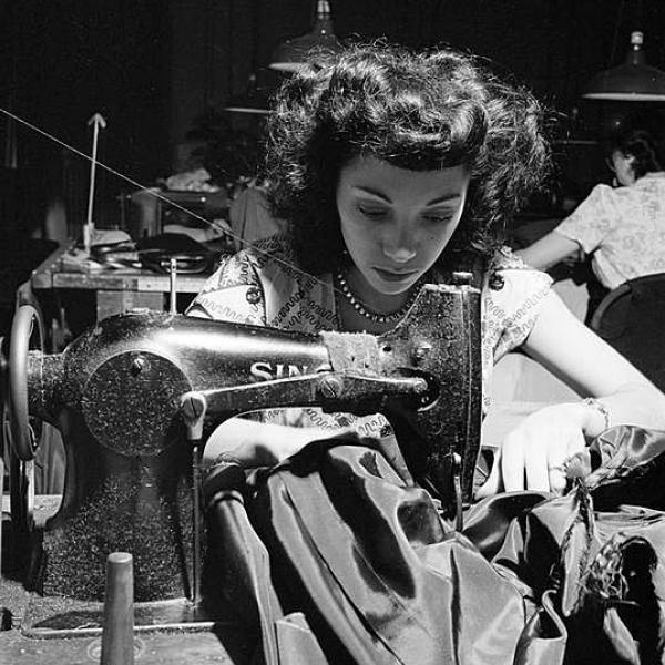 Photograph is black and white and shows a young woman working in a garment factory in 1949. The photograph was taken for Look magazine.