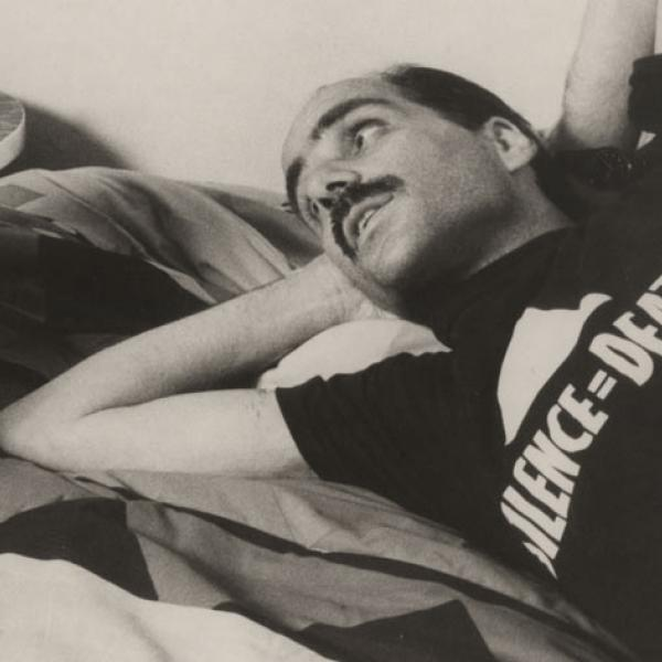 Close-up of a male AIDS patient wearing an ACT UP t-shirt and lying on a bed