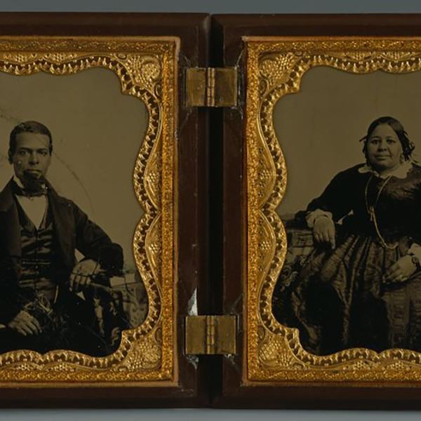경첩이 달린 나무와 금색 케이스에 흑백 사진 XNUMX 장. 남자 (왼쪽)와 여자 (오른쪽)는 검은 색이며 세련된 검은 색 양복과 드레스를 입는다.