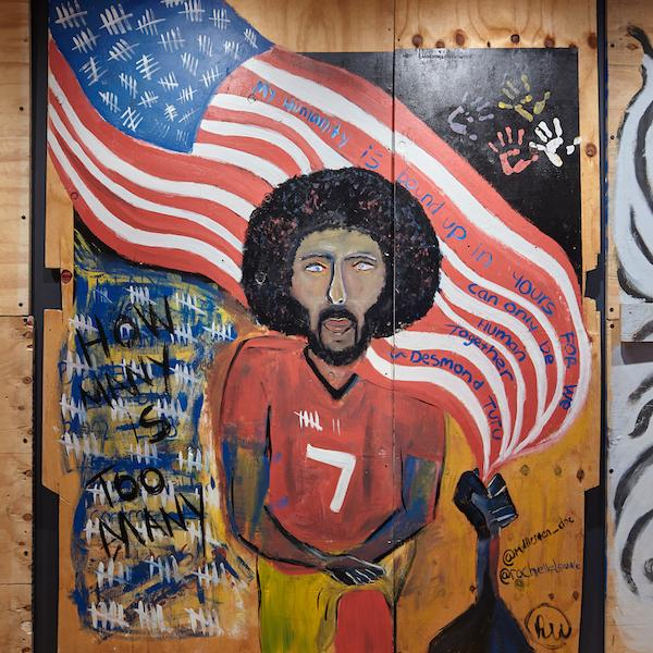 Plywood artwork created during the COVID-19 pandemic and racial justice uprisings in 2020. Colin Kaepernick is in the foreground, on bended knee, with the American flag waving behind him.