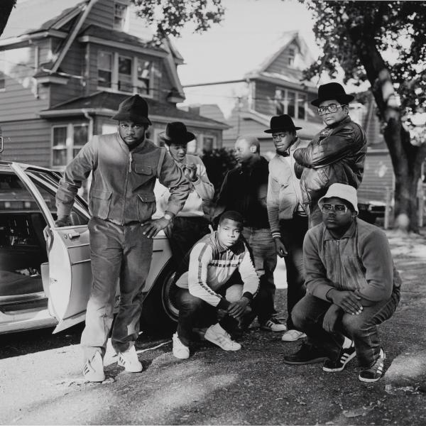 RUN DMC with a group of men posing next to a car in Hollis, Queens.