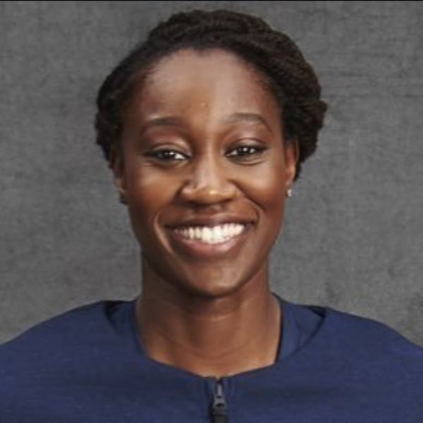 Tina Charles head shot - gray background with blue shirt