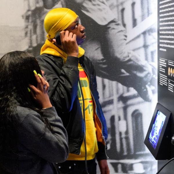 The Museum of the City of New York's Logo; Two individuals listen to audio recordings in front of a museum exhibition; StoryCorps' Logo for the Great Thanksgiving Listen