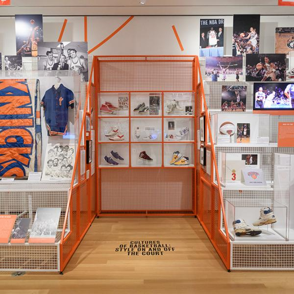Installation photo of the City/Game exhibit, featuring sneakers, basketball jerseys, and photographs of basketball players.