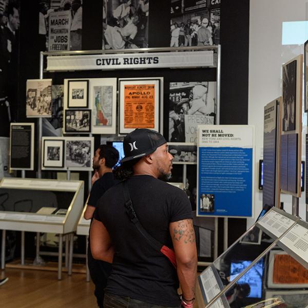 Un visiteur de l'exposition Activist New York du Museum of the City of New York examine des artefacts sur l'histoire du changement social dans la ville.