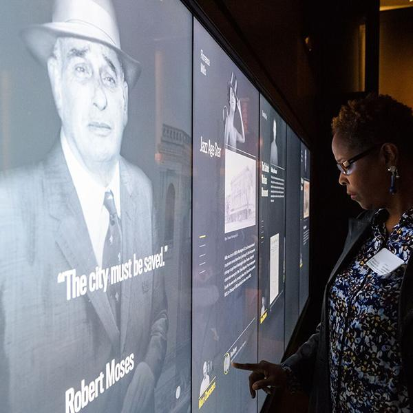 An educator examines a touchscreen that showcases the stories of people from NYC's past.