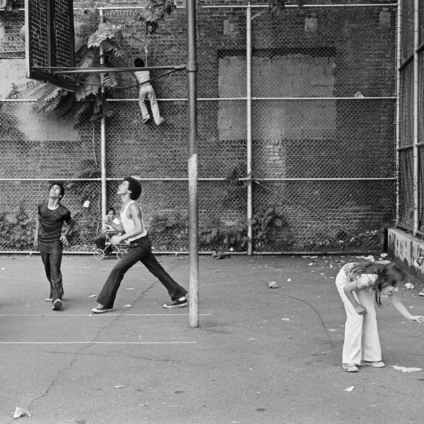 Photograph of people playing basketball in basketball court between two buildings, woman and child in front