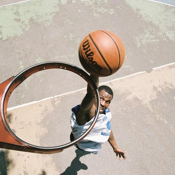ネットなしのバスケットボールのフープの上からの眺め、プレーヤーがフープを通してバスケットボールをダンクしようとしているところ