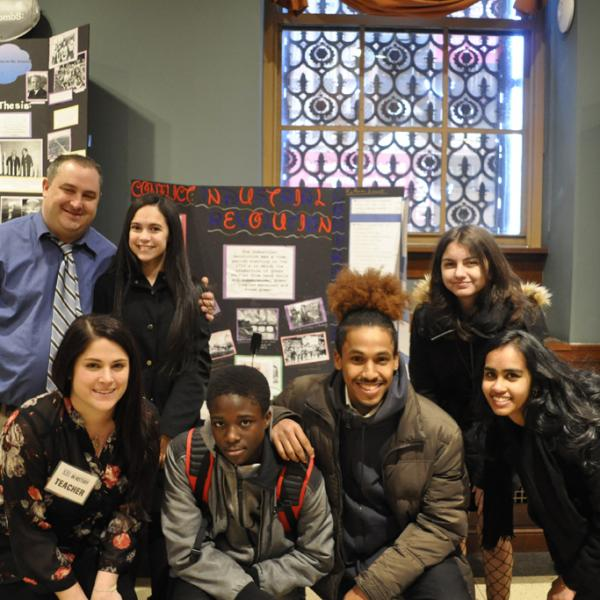 Five high school students and two teachers pose smiling for the camera in front of an exhibition board at the 2018 New York City History Day.