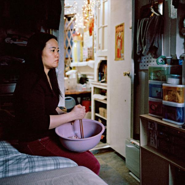 Una mujer china revuelve comida en un tazón mientras ve una telenovela china. Ella está sentada en una cama en un departamento.