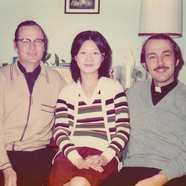 Color photograph of Fathers Denis Hanly (right) Joanna Chan, and Richard Grillo (left), sitting in a living room.