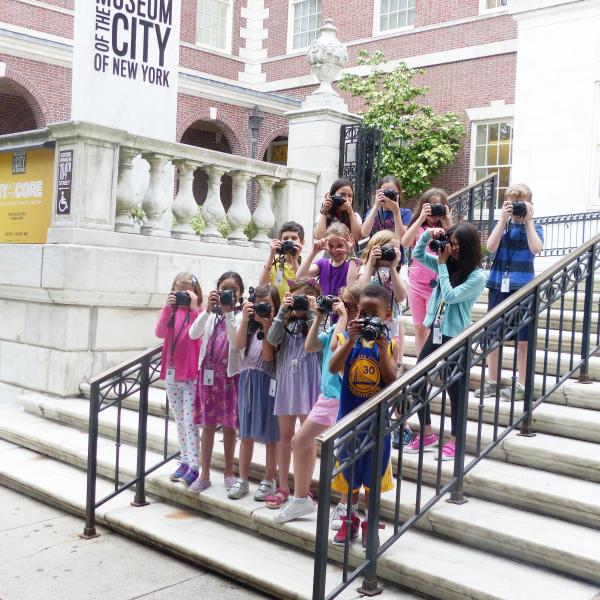 Fourteen children stand in three rows, they are all holding cameras up to the faces. They are standing on the steps at the entrance to the Museum of the City of New York. On the left above the children is a sign reading Museum of the City of New York.