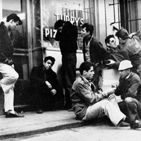 A group of young men hanging outside of a pizza parlor. Some sit on the street while others stand or lean on the wall. Two appear to be pushing one another.