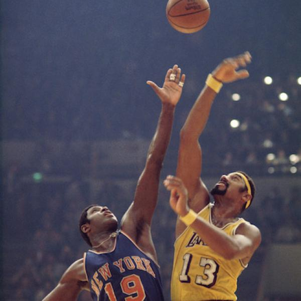 Willis Reed and Wilt Chamberlain tip off at the start of a basketball game