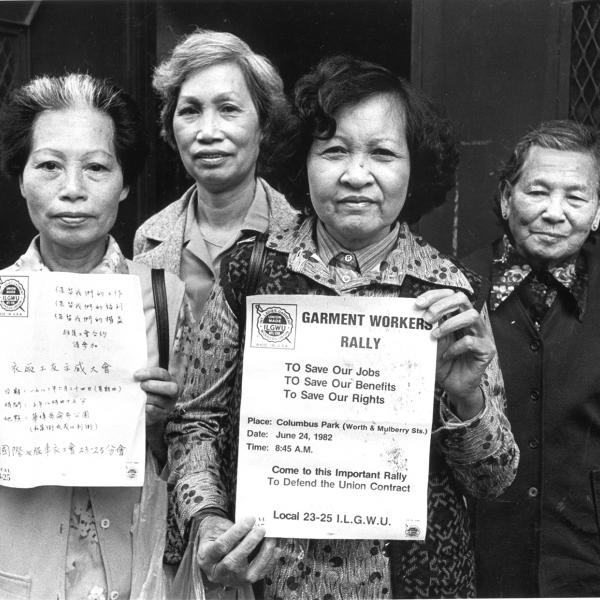 Members of the labor union ILGWU Local 23-25 look directly into the camera and hold up English and Chinese-language flyers in support of the strike against garment factories in New York City's Chinatown.
