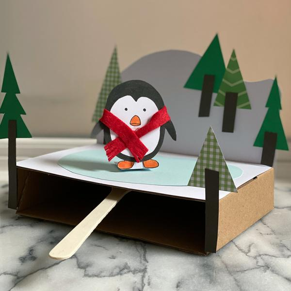 A photo of a craft project using paper and cardboard to create a penguin wearing a scarf skating on a frozen field of ice.