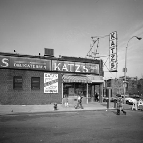 Exterior view of Katz's Delicatessen at the intersection of Ludlow and Houston Streets with a few people walking past.