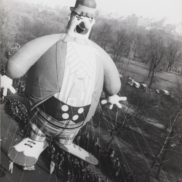 Large balloon of a clown floats about city streets, with a crowd of onlookers below.