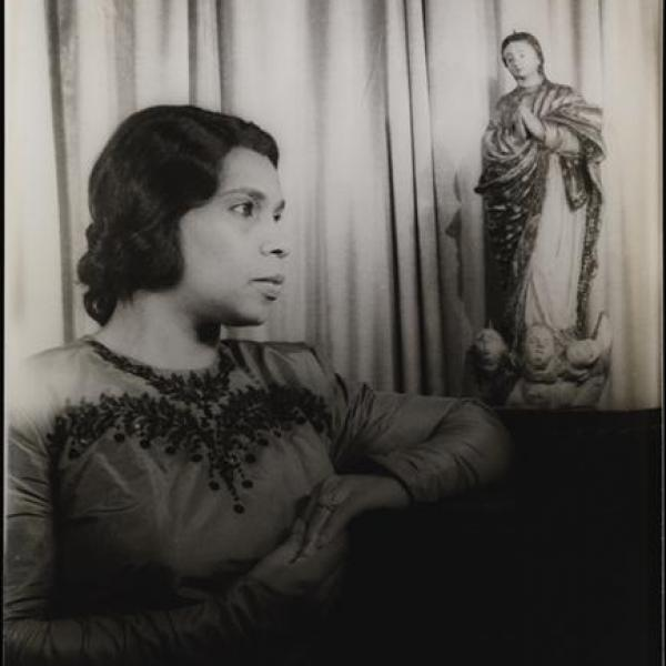 Black and white portrait of Marian Anderson in front of a curtain. Her arms rest on a dark surface, with a statue of a religious figure next to her left elbow.