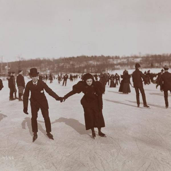 An outdoor museum photo of a man and women holding hands while ice skating with a group of people.
