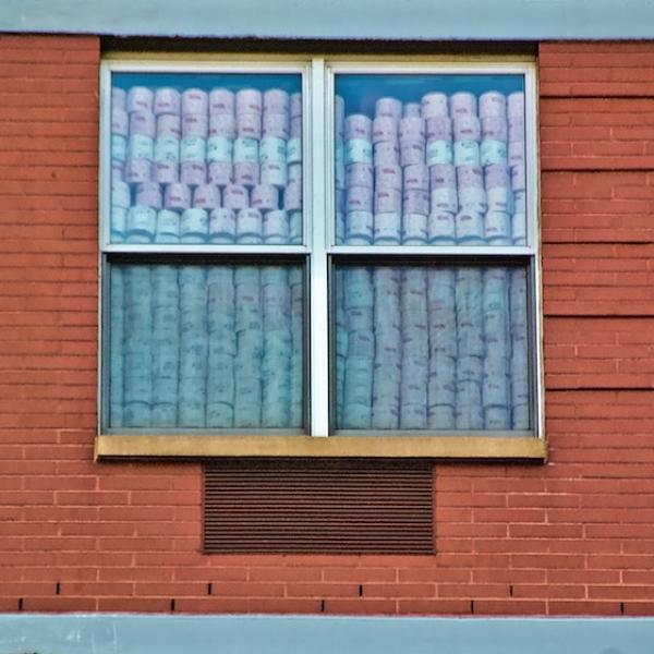 Two windows in an brick building that are filled with stacks of toilet paper rolls.