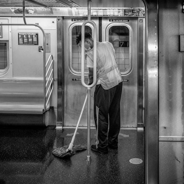 A man with a mop cleans the floor of a subway car in front of a subway door.