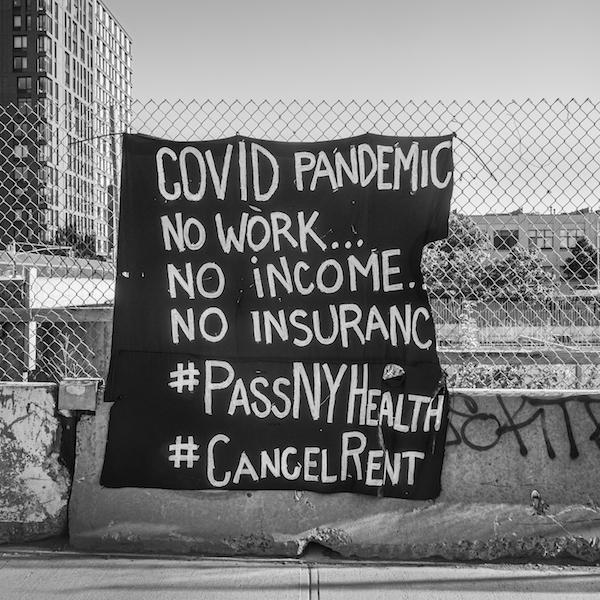 "A black and white photograph of a sign on a fence that reads ""COVID PANDEMIC No work....No Income...No Insurance...#PassNYHealth #CancelRent"""