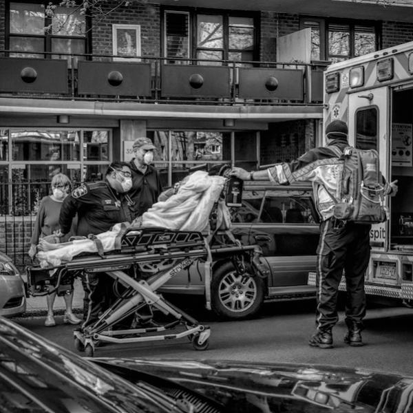 A person on a stretcher is being wheeled into an ambulance assisted by three medical workers. A fourth person stands nearby.