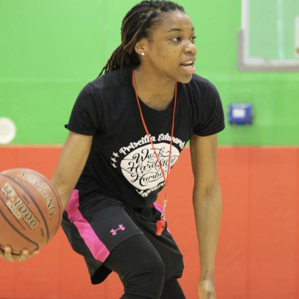 Priscilla Edwards holds a basketball in her right hand, in a low dribbling stance, she is facing a group off camera, speaking to them.