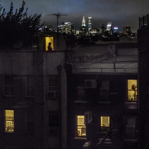 萨利·戴维斯(Sally Davies)在东五街的公寓的后视图,晚上带有照明窗户。