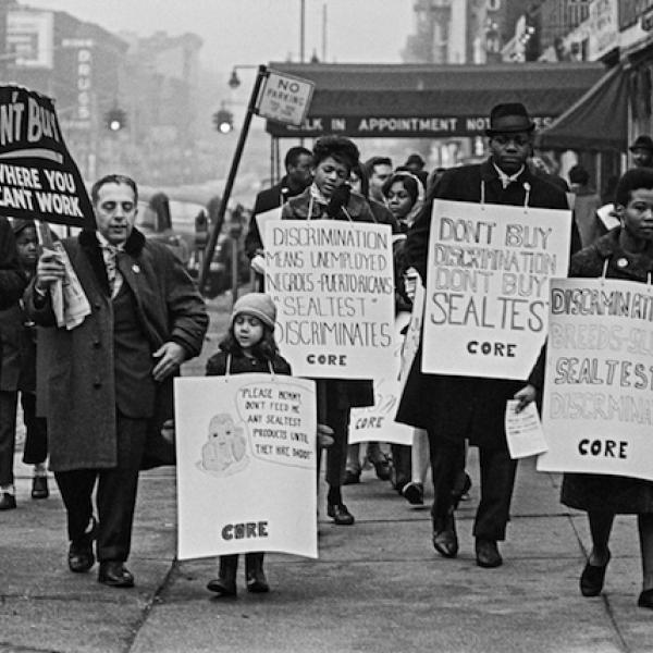 A black and white photograph of people from Brooklyn CORE walking with signs in a boycott against Sealtest Dairy Company in 1963.