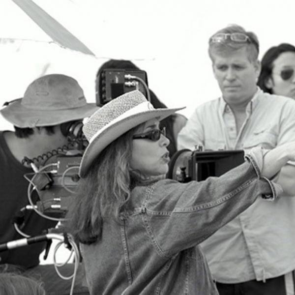 A black and white image of film director Susan Seidelman sitting in front of a camera with a group of 3 people. She is pointing to the right