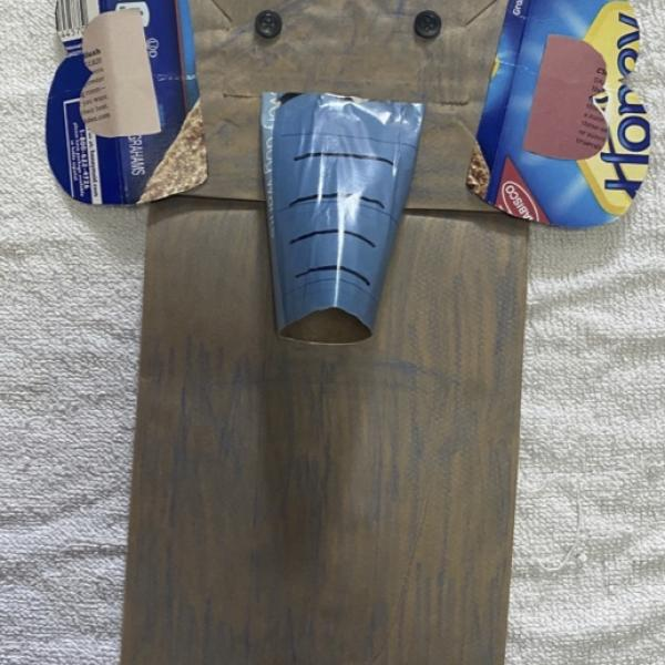 Brown paper lunch bag turned into a hand puppet designed to look like an elephant. It has two black buttons for eyes, two ears made from a blue cardboard food container, and a trunk made from a toilet paper roll covered in blue magazine paper.