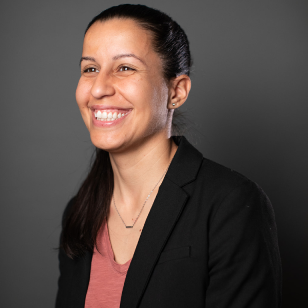 A headshot of Tiffany Cabán, who is wearing a blush pink shirt and black blazer smiling against a grey background.