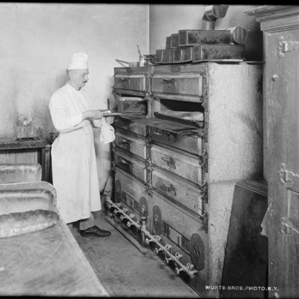 A photo by Wurts Bros. (New York, NY) of a restaurant chef using a bread oven.