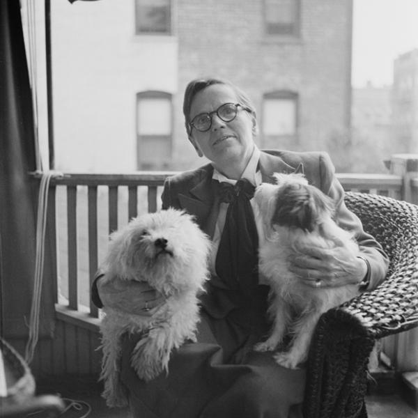 Florence Ripley Mastin sitting on a porch with two dogs in her lap.