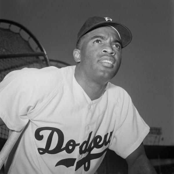 Baseball player Jackie Robinson wears his Brooklyn Dodgers uniform and hat, with a baseball stadium in the background
