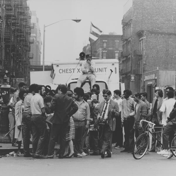 A crowd gathered in front of an X-ray unit truck. A man sits on the truck, staring at the camera.
