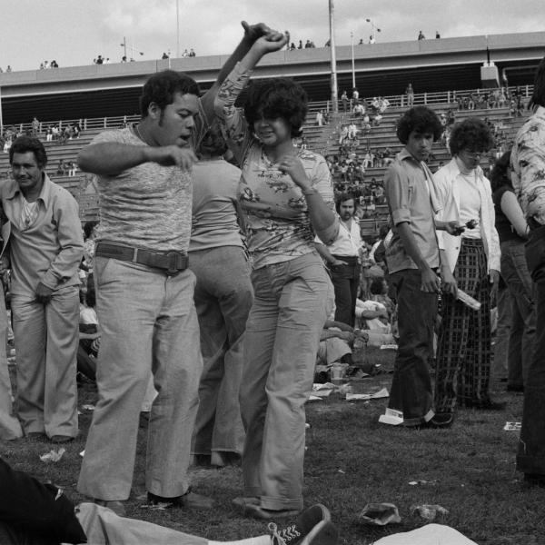 A casually dressed couple dances salsa with people in the background on Randall's Island in 1974.