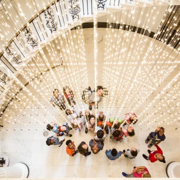 "A group of students stand under the Museum's light installation, ""Starlight."""