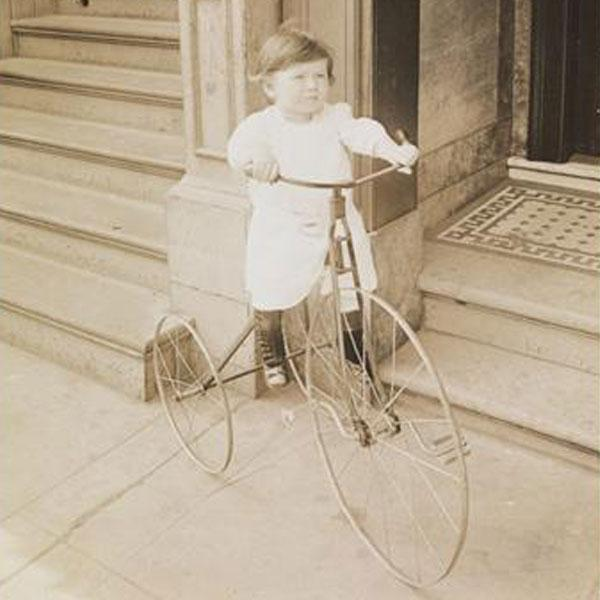 Photograph of a bike carriage driver, biking down the streets of New York City as there is oncoming traffic.